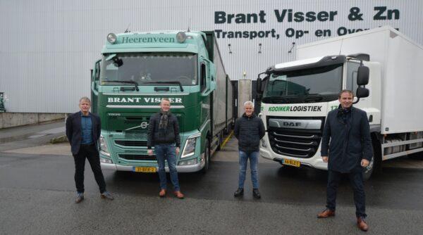 vier personen voor twee vrachtwagens kooiker logistiek