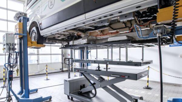 elektrische bestelbus man op de brug in de garage
